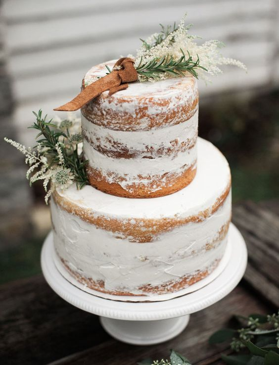 a semi naked winter wedding cake topper with herbs and leather for a rustic celebration