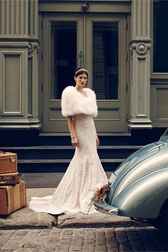 an embellished wedding dress with a train, a white fur wrap, a jeweled headpiece and a bold lip