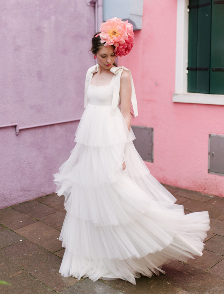 The bride was wearing a layered tiered dress with large bows on her shoulder and an oversized peony headband