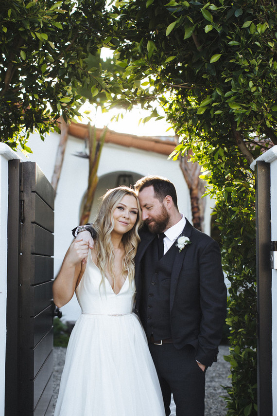 The groom was wearing a black three-piece suit with a tie and a white boutonniere