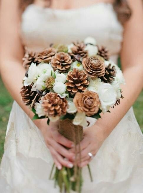 a cute rustic bouquet with pinecones and white blooms looks sweet and winter-like