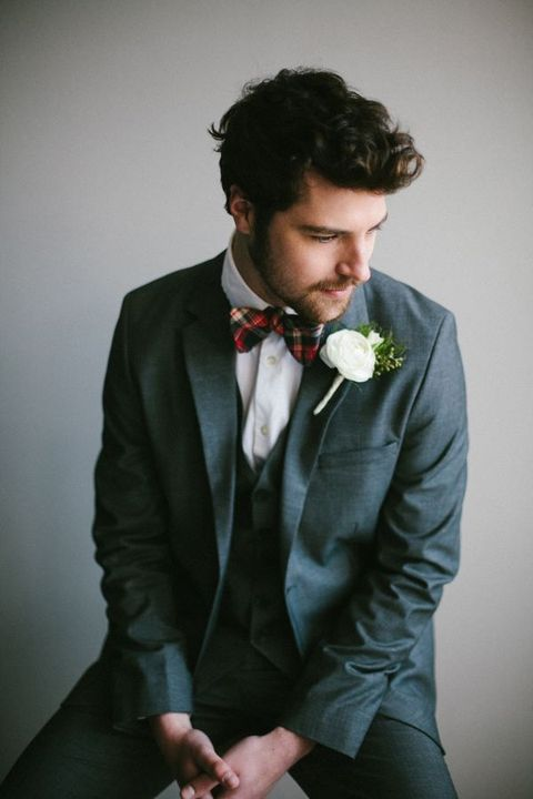 a groom in a grey suit and with a plaid tie for a slight but cute touch of the festive spirit