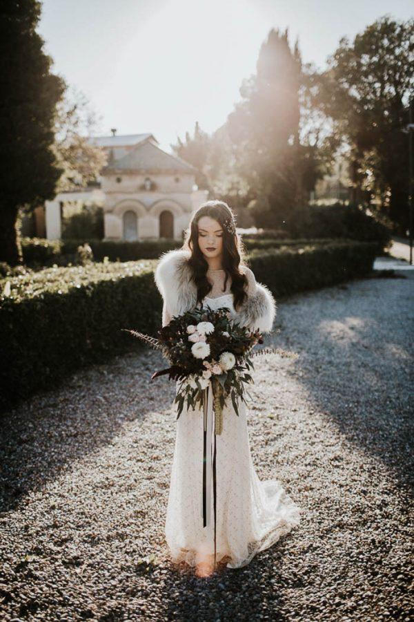 glam-Braut-look mit einem verzierten Kleid mit einer illusion Ausschnitt, Pelz Verheimlichung, eine dunkle Lippen und eine glitzernde Kopfbedeckung