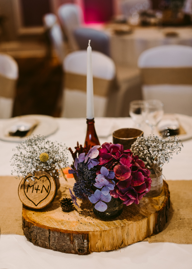 A pretty wedding centerpiece of a wood slice, some bold blooms, a pinecones and candles
