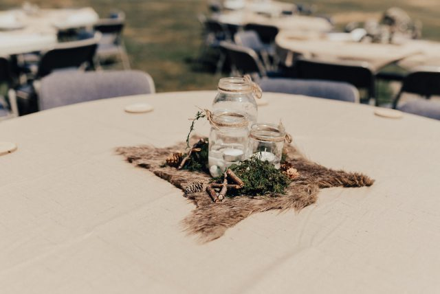 The table decor was done with fur, branches, pinecones and mason jars