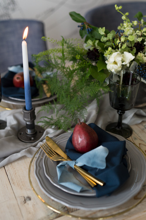 The tablescape was done with a grey table runner, grey plates, a sheer charger with a gold rim, ombre blue candles and black glasses