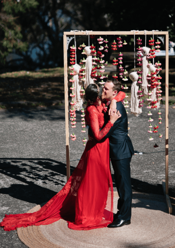 The wedding arch was a wooden one with large tassels hanging and colorful bloom garlands