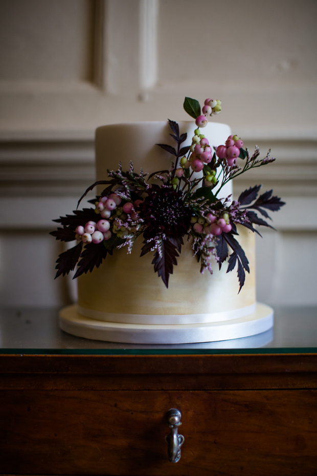 The wedding cake was done in ivory and gold, with blooms, dark foliage and berries