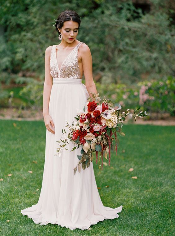 a blush wedding dress with a deep V-neckline, a sequin bodice and matching earrings for a girlish glam look