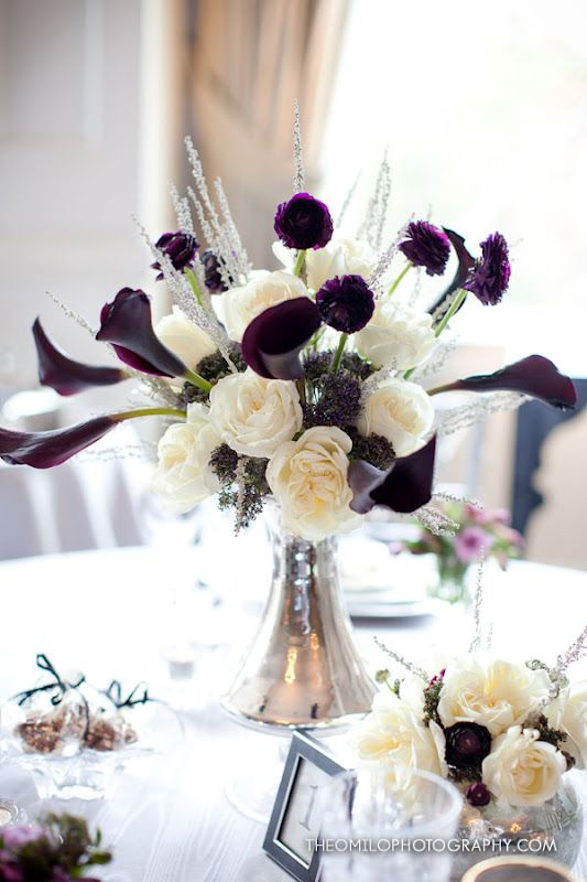 a floral centerpiece of white roses and deep purple callas looks unusual and bold