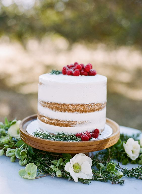 a holiday inspired winter wedding cake topped with fresh raspberries for a Chrstimas wedding