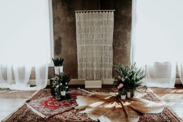 The ceremony space was done with a lot of texture, a macrame backdrop, rugs, greenery and blooms for a boho setting