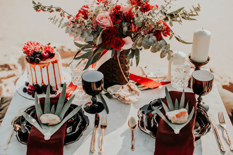 The desert picnic table was set with black plates, large leaves, gold cutlery and black goblets