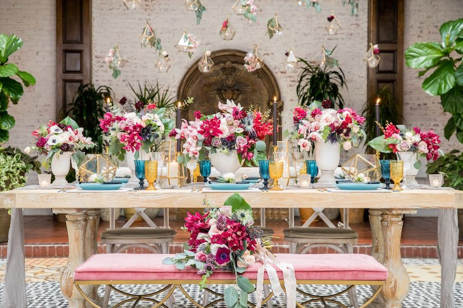 The wedding tablescape was done with bold colors   fuchsia, pink, blue, gold and burgundy