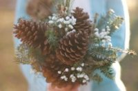 07 a bouquet maded of large pinecones, evergreens and baby's breath for a rustic winter bride