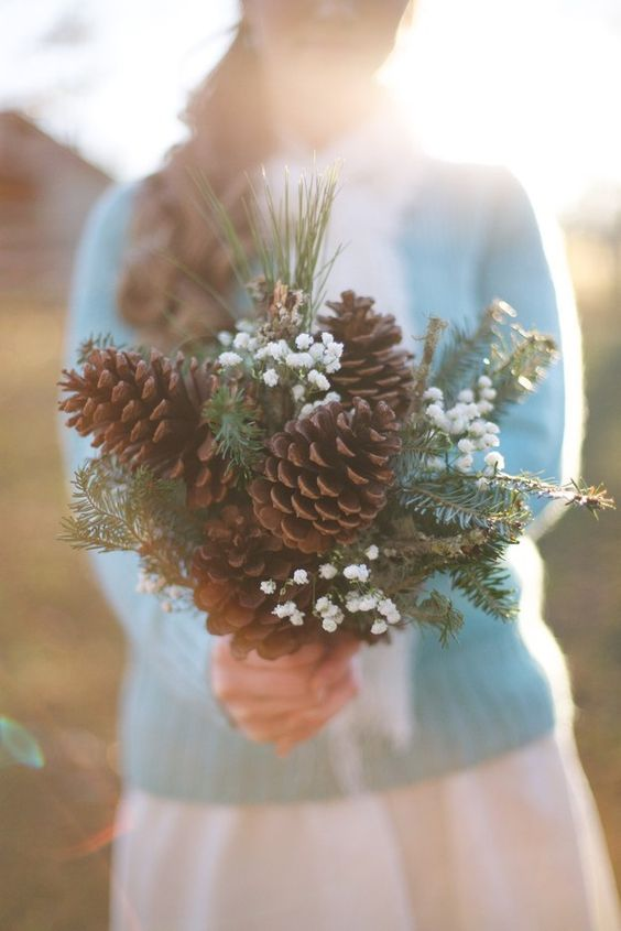 a bouquet maded of large pinecones, evergreens and baby's breath for a rustic winter bride