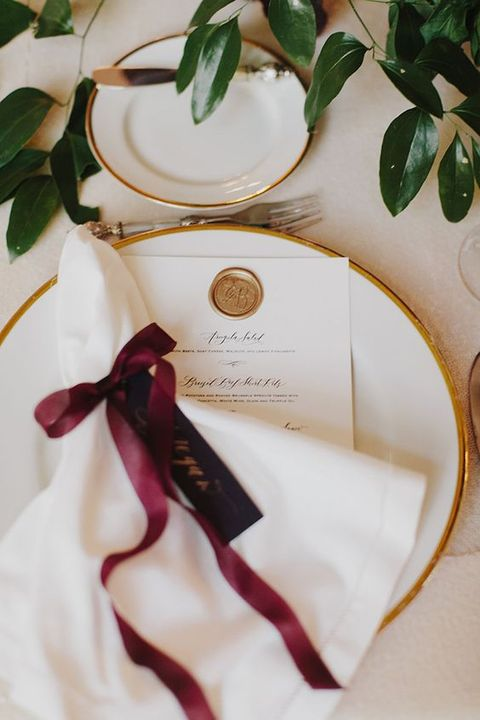 a chic tablescape with gold rim plates, greenery and napkins with burgundy bows