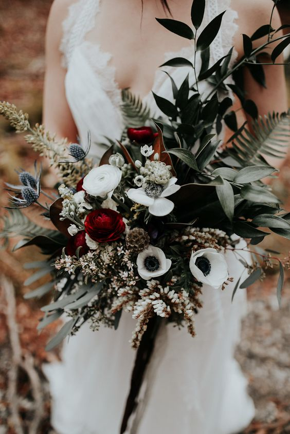 a dark bouquet with thistles, red and white blooms and dark greenery