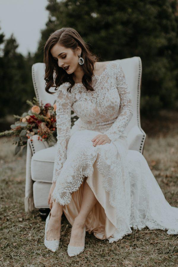 eine Spitzen Hochzeit Kleid, statement-Ohrringe, verziert pumps und eine dunkle Lippe für einen luxuriösen winter-Hochzeits-look