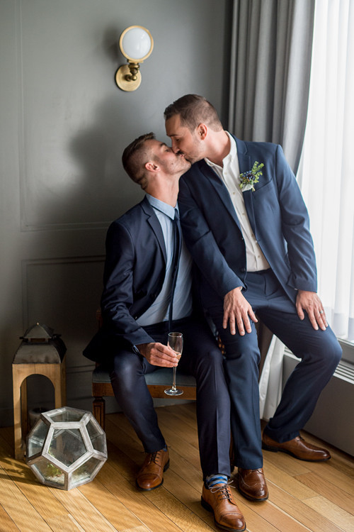 The grooms were wearing navy suits, brown shoes and boutonnieres