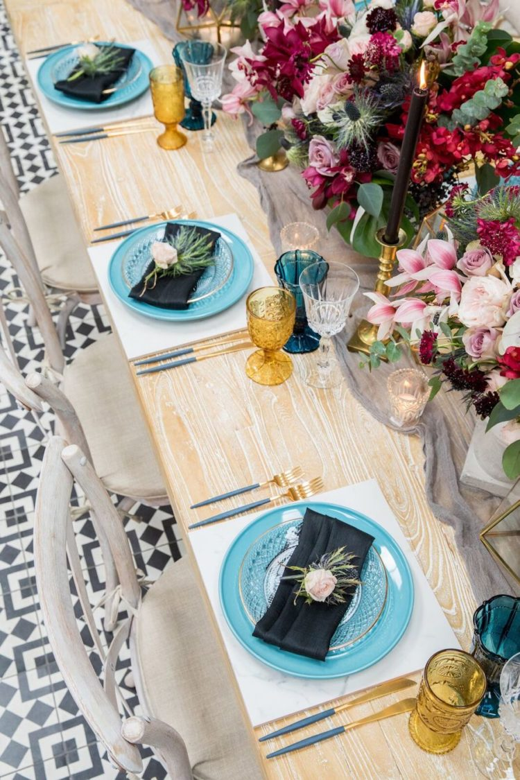 The tablescape features blue plates, blue and gold glasses, black candles in gold candle holders and various lush florals