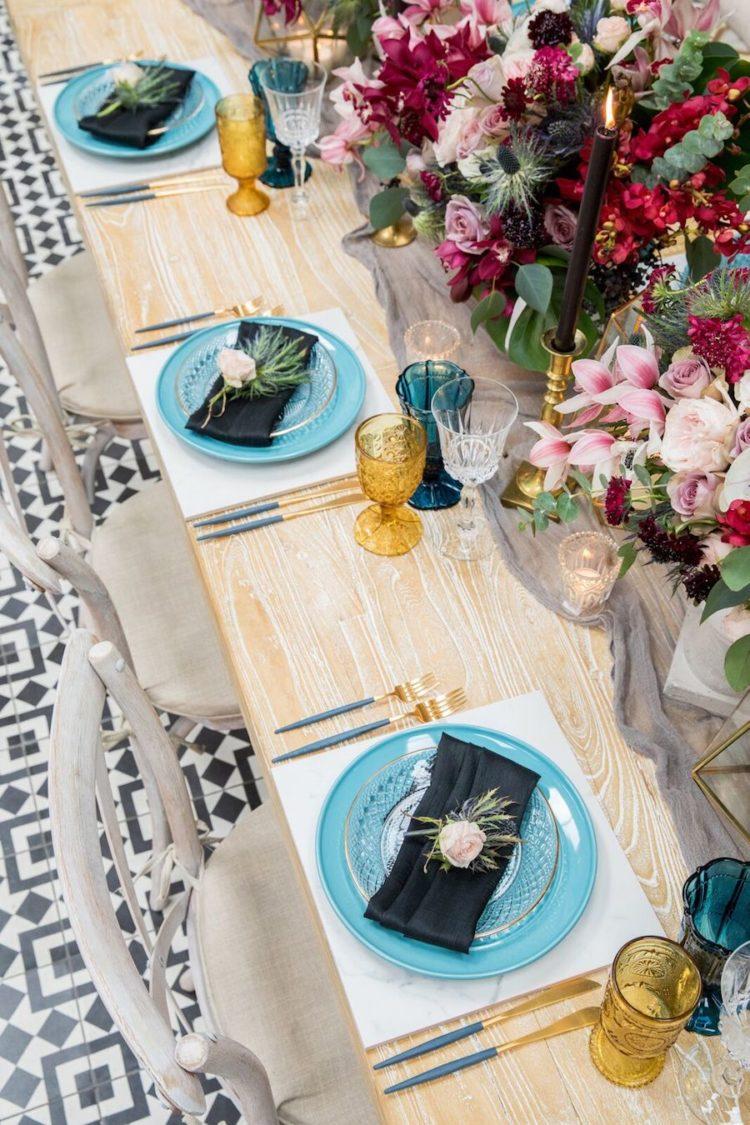 Die tablescape features Blaue Platten, Blaue und gold-Brille, schwarze Kerzen in gold Kerzenhalter und verschiedene üppigen florals