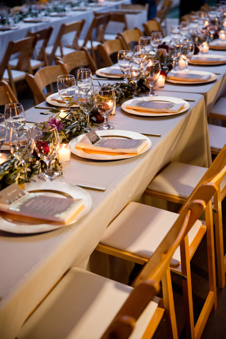 The wedding reception was done with a greenery and bloom table runner and candles
