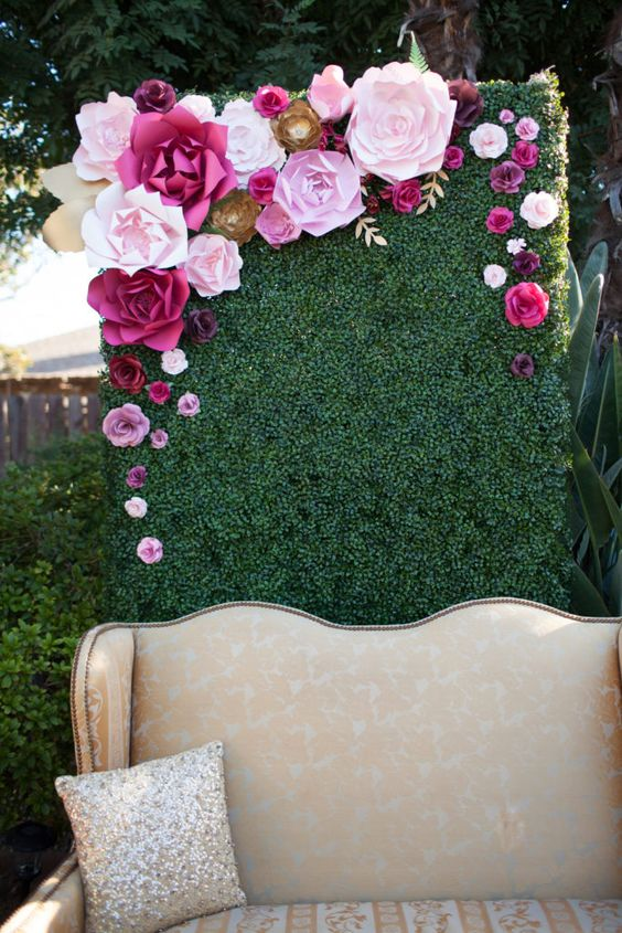 a chic photo booth with a green wall topped with paper flowers in pink and fuchsia colors, and a refined sofa