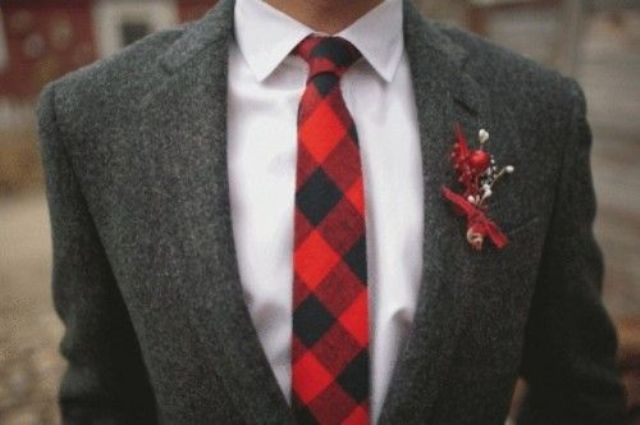 a groom wearing a grey tweed suit and a plaid tie with a red boutonniere