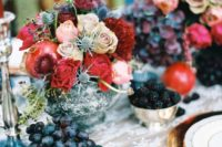 08 a lush centerpiece with dusty pink roses, thistles, pomegranates and red blooms for a colorful winter celebration
