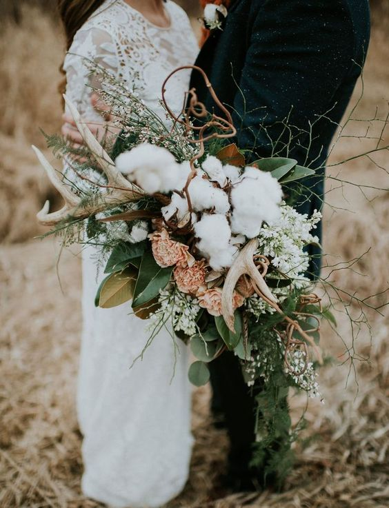 a textural woodland bouquet with antlers, cotton, gold and green leaves, pink and white blooms