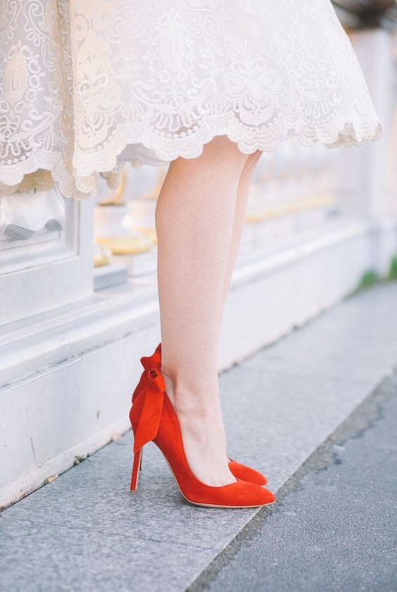fiery red suede wedding shoes with bows on the backs look very chic and timeless