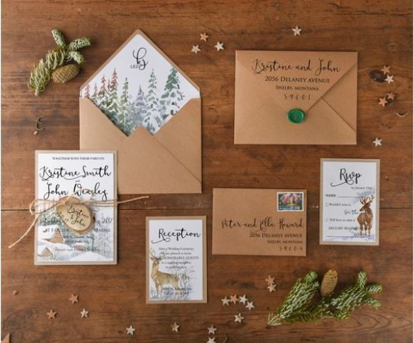 gorgeous Christmas wedding invites on amber paper, with deer, snowy forests and small houses