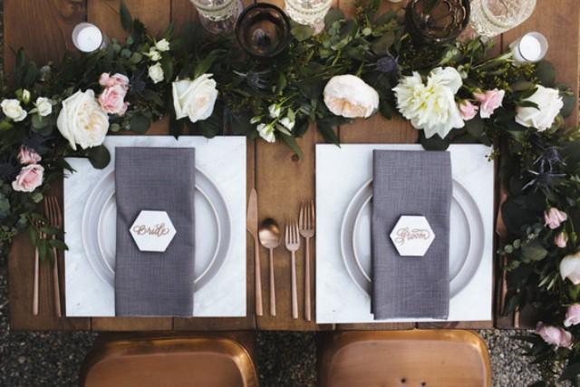 The sweetheart table was decorated with a lush bloom and greenery garland, geo cards, copper cutlery and grey napkins