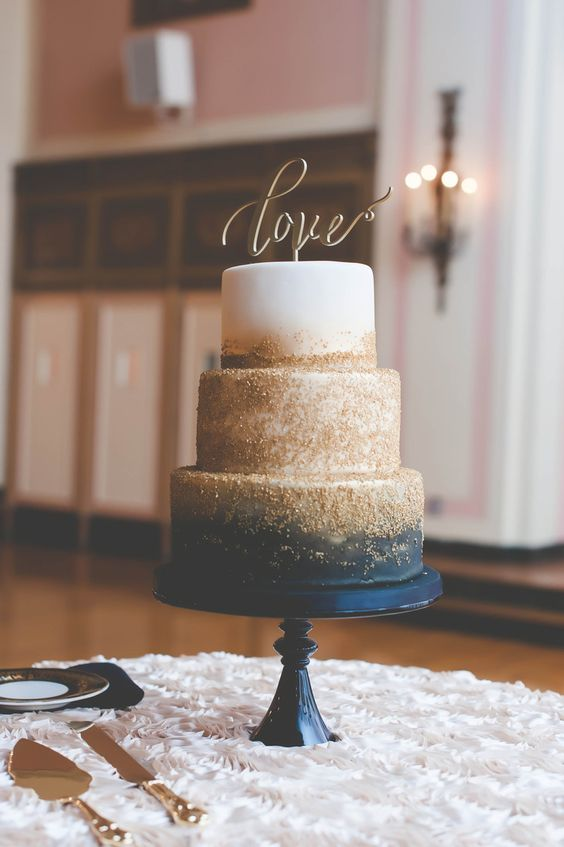 a glam wedding cake with navy, gold glitter and white and a calligraphy topper