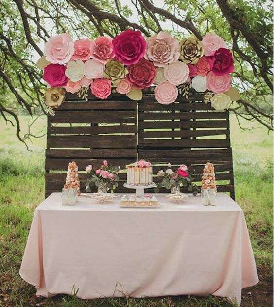 a paper flower backdrop for the cake table done in pink, fuchsia and white