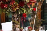 09 a tall vase filled with moss and pinecones and with red blooms brings a winter feel
