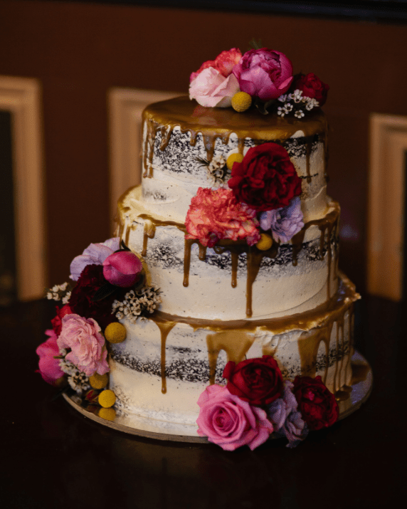 The wedding cake was a naked one, with salty caramel drip and bold blooms on top