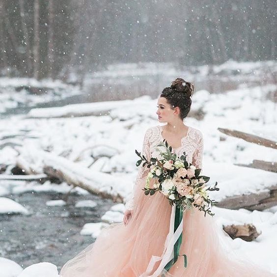 a lace bodice wedding dress with long sleeves and a pink flowy skirt to stand out in the snow