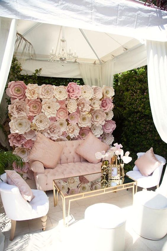a large paper flower wall in pink and blush for a beautiful glam wedding lounge