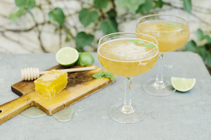 Here's a simple and cute cocktail table with cocktails, limes and honey