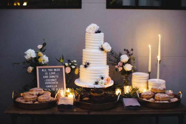 Die dessert-Tabelle zeigte einen weißen Kuchen verziert mit Blumen und verschiedenen glasierten donuts
