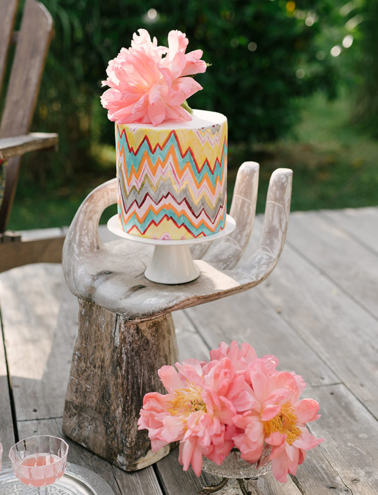 the wedding cake was a colorful one with bold geometric patterns and a fresh peony on top