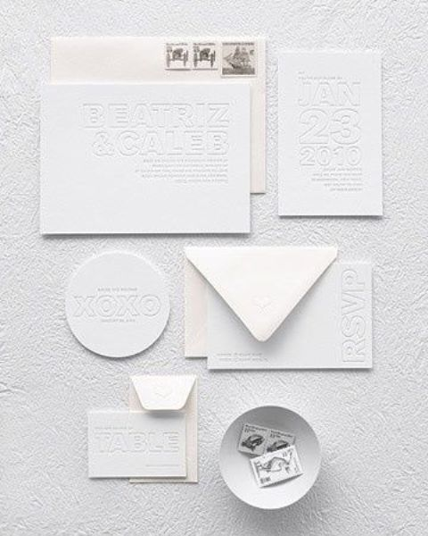 a minimalist all-white letterpressed invitation suite is a unique and very eye-catchy idea