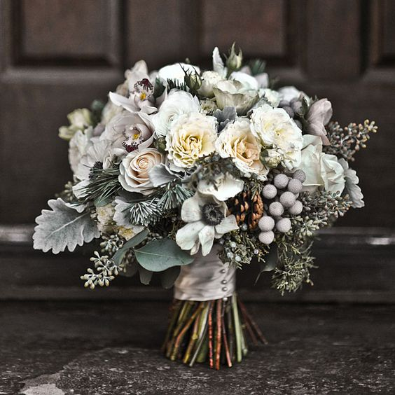 mini cymbidium orchids, silver brunia, juniper sprigs, pine boughs, anemones, pinecones, garden spray roses, seeded eucalyptus, blush roses, and dusty miller