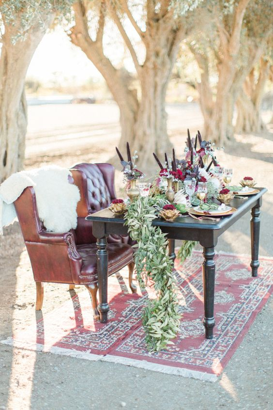 a boho lux tablescape with a greenery table runner, gold vases, plum-colored blooms and feathers