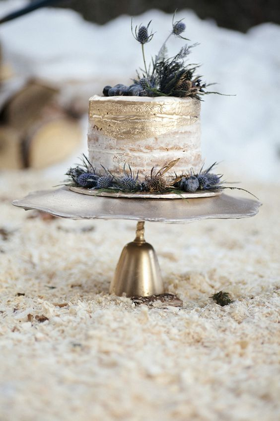 a naked wedding cake with gold leaf decor, blueberries and thistles looks dreamy and very winter-like