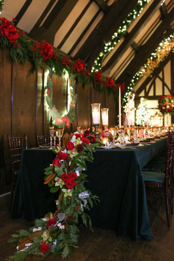 a cascading holiday-inspired table runner with magnolia leaves, evergreens, red roses and pinecones for a festive wedding