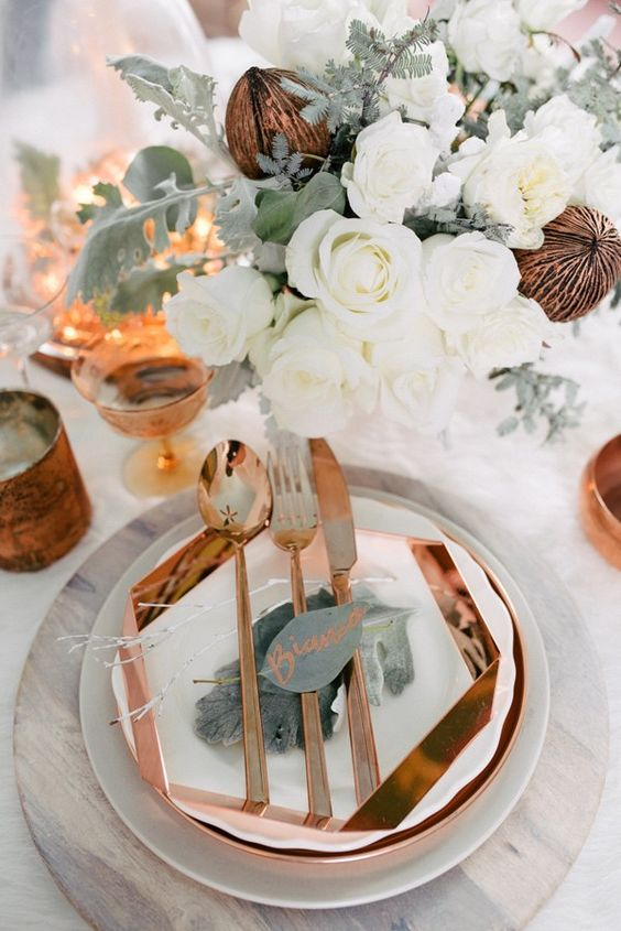 eine glam-Ort-Einstellung mit üppigen weißen Blüten, Kupfer Besteck und ein Ladegerät und Gläser
