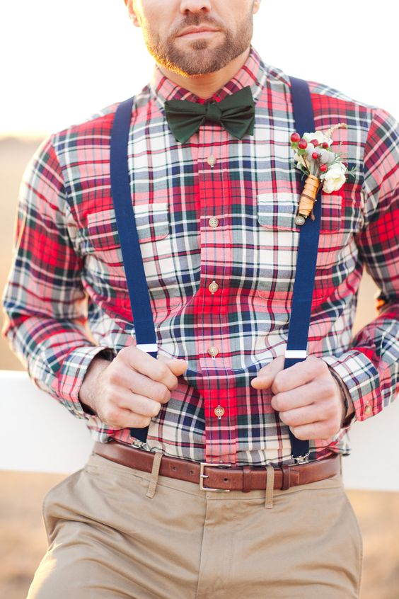 the groom rocking a plaid shirt, navy suspenders, a black bow tie and neutral pants